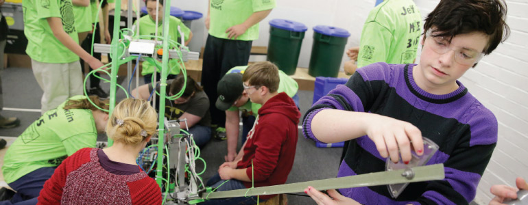 "Liz Frick, 17, co-team president of Team ""Miracle Workerz,"" works on the hook that grabs containers on the robot ""ToMOEhawk"" at Chestnut Run. She is from Ursuline Academy. (Photo by Tim Hawk)"